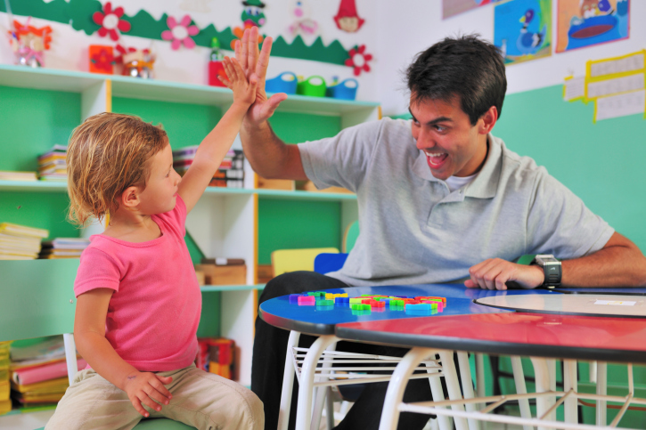 Preschool teacher and child giving a high-five